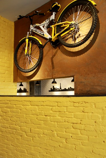 The massive yellow wall with a bicycle hanging on rustic metal surface, depicting an iconic image of the restaurant, as well as creating privacy. Image Courtesy: Khandaker Ashifuzzaman