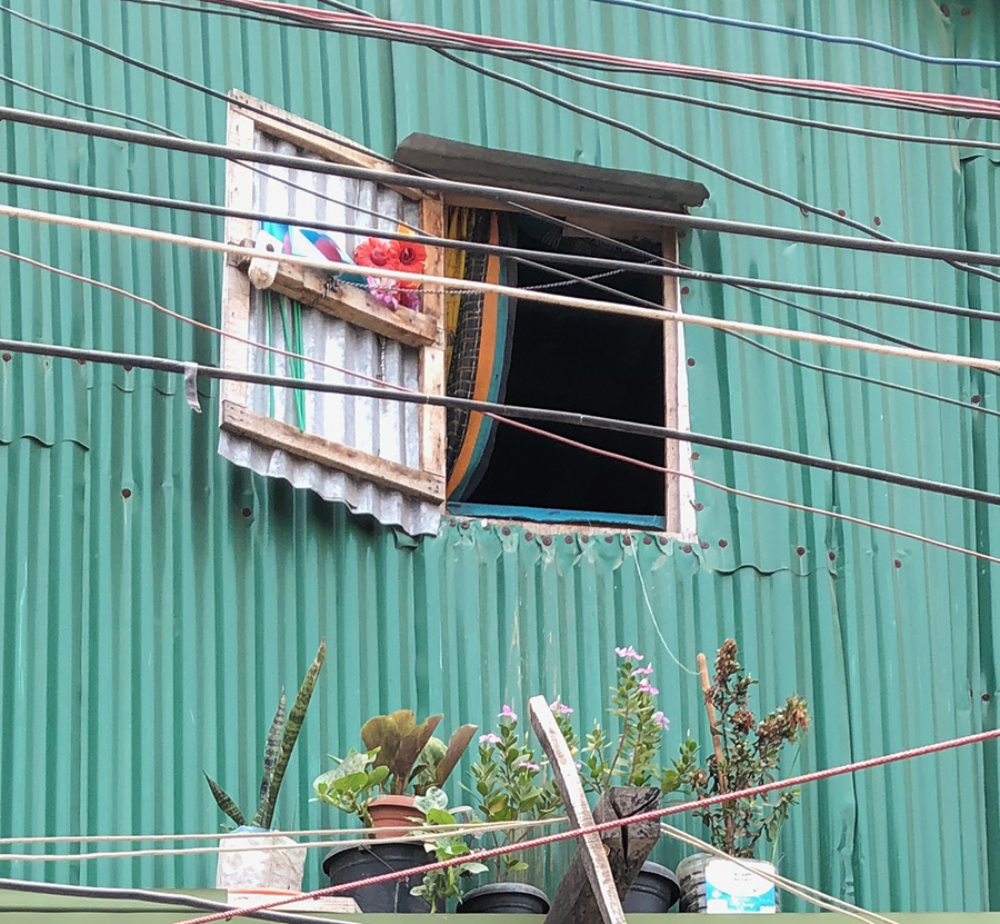A flower in a slum window - slums are places of affordable housing and dreams for a better life | Courtesy: Kim Dovey